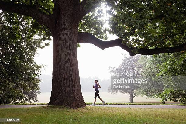 woman jogging in suburban park - montclair stockfoto's en -beelden