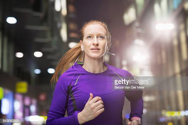Woman jogging in urban street at night.