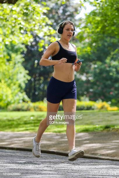 A woman jogging on a warm and sunny day in Finsbury park during the COVID19 lockdown The government has relaxed the restrictions on coronavirus...