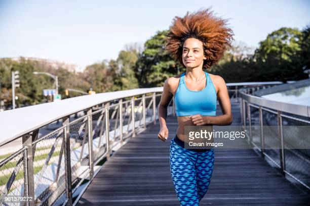 woman jogging on bridge against sky - bra top stock pictures, royalty-free photos & images