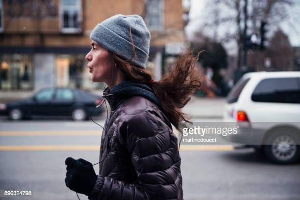 """woman jogging on city sidewalk in winter. - """"martine doucet"""" or martinedoucet stock pictures, royalty-free photos & images"""