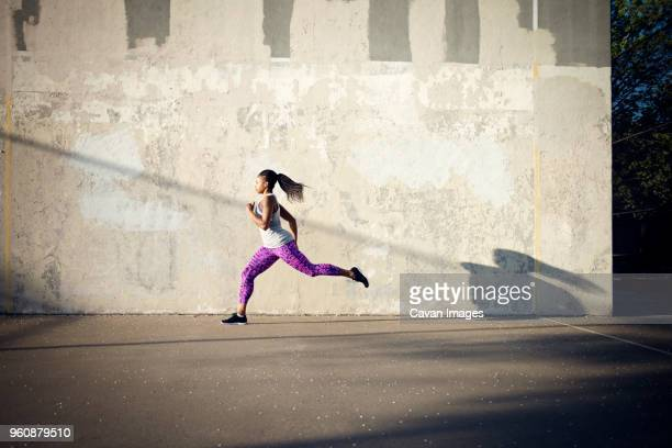 woman jogging on street by wall - track event stock pictures, royalty-free photos & images