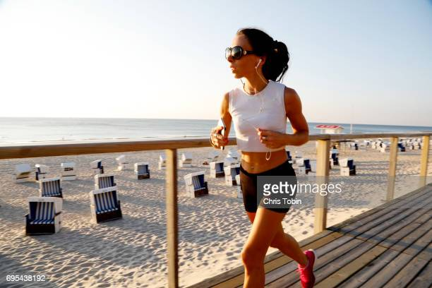 Woman jogging on the beach boardwalk while listening to music on smartphone