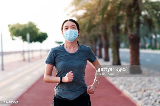 woman jogging on the running track wearing protective mask - illness prevention stock pictures, royalty-free photos & images