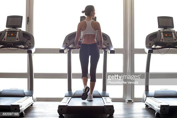 woman jogging on treadmill at gym - treadmill stock pictures, royalty-free photos & images