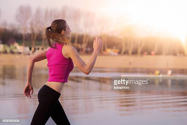 Woman jogging outdoors by the beach during the day
