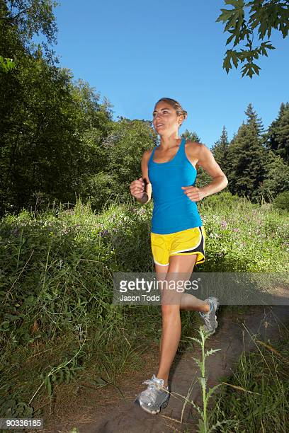 woman jogging through meadow in forest - jason todd stock photos and pictures