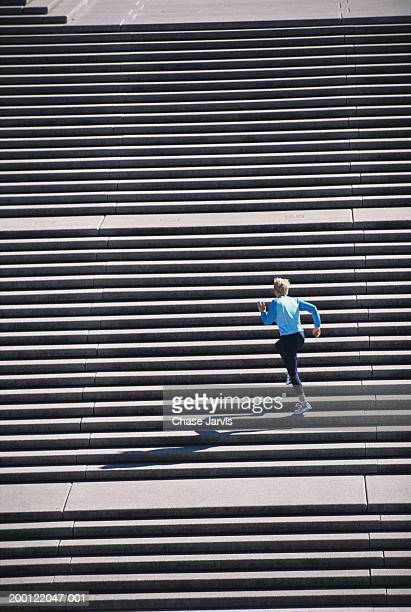 Woman jogging up flight of stairs, outdoors, elevated view