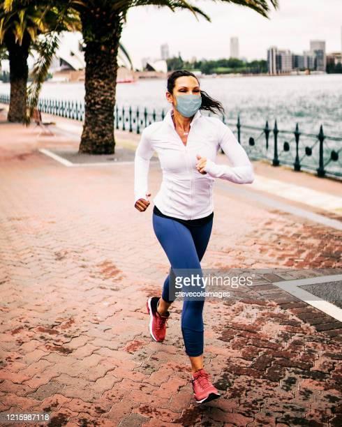 donna che fa jogging indossando la maschera sanitaria per la protezione. - attività foto e immagini stock