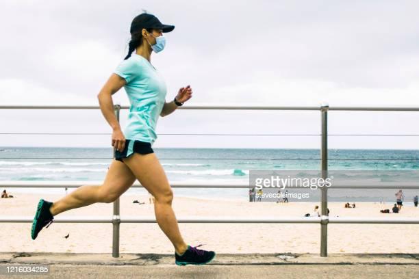 woman jogging wearing healthcare mask. - coronavirus australia stock pictures, royalty-free photos & images