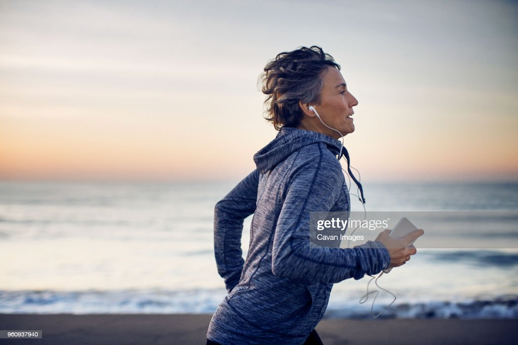 Woman jogging while listening music at beach against sky : Stock Photo