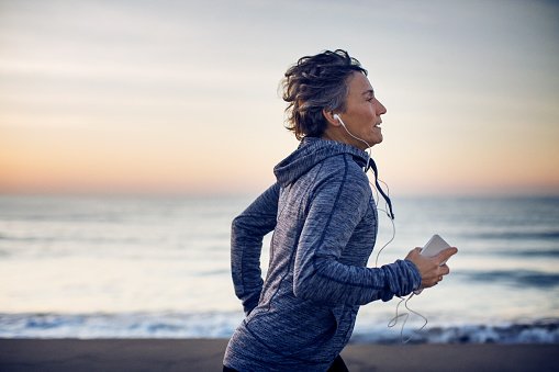 Woman jogging while listening music at beach against sky - gettyimageskorea