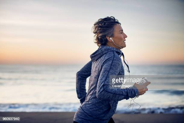woman jogging while listening music at beach against sky - actieve ouderen stockfoto's en -beelden