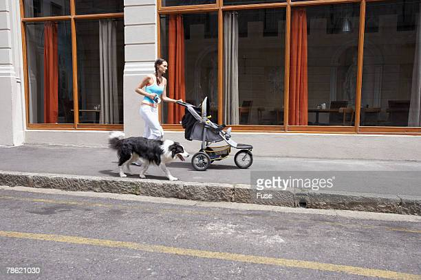 Woman Jogging with Baby Stroller and Dog