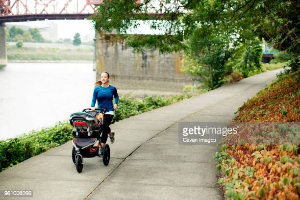 Woman jogging with baby stroller on footpath by river