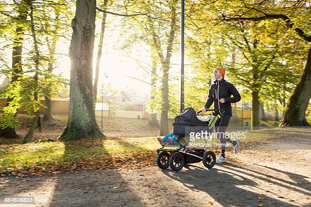 Woman jogging with baby stroller on road at park