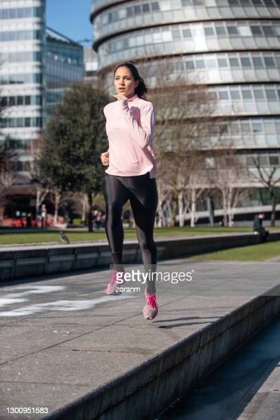 woman jogging with london's city hall in background - running stock pictures, royalty-free photos & images