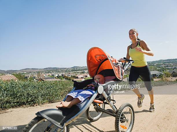 woman jogging with stroller - three wheeled pushchair stock pictures, royalty-free photos & images