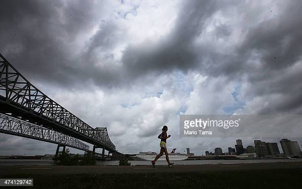 A woman jogs along a levee along the Mississippi River with the city skyline in the distance on May 16 2015 in New Orleans Louisiana The tenth...