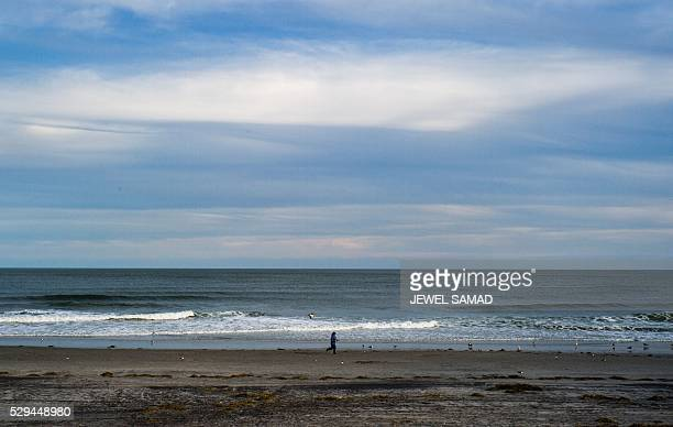 Woman jogs along an empty beach in Atlantic City, New Jersey, on May 8, 2016. Atlantic City, the famous US gambling resort town and setting for hit...