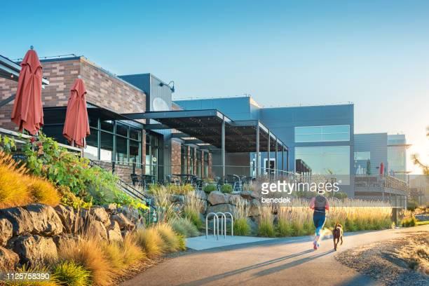 woman jogs at spokane river promenade in downtown spokane washington - spokane stock pictures, royalty-free photos & images