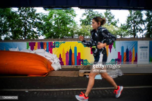A woman jogs next to flood barriers used to prevent flooding at the South Street Seaport as the city gets ready for tropical storm Isaias on August 4...
