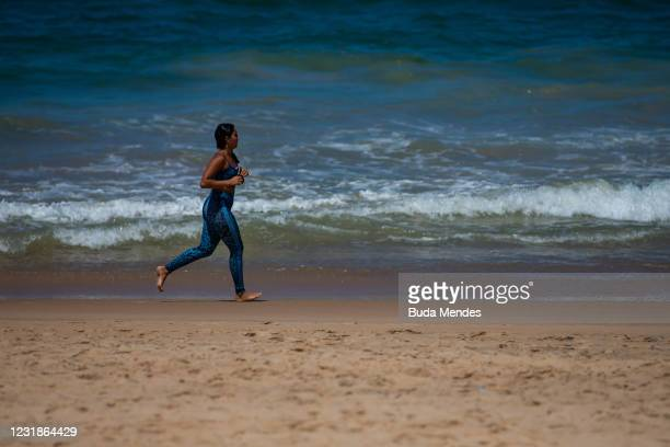Woman jogs on a beach in Macae, only 179 km away from the city of Rio de Janeiro where beaches are closed to curb the spread of COVID-19 on March 20,...