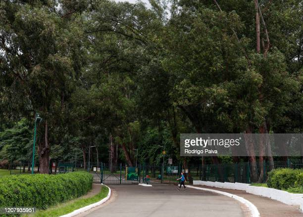 A woman jogs outside the gates of Ibirapuera Park during a lockdown aimed at stopping the spread of the coronavirus pandemic on March 21 in Sao Paulo...