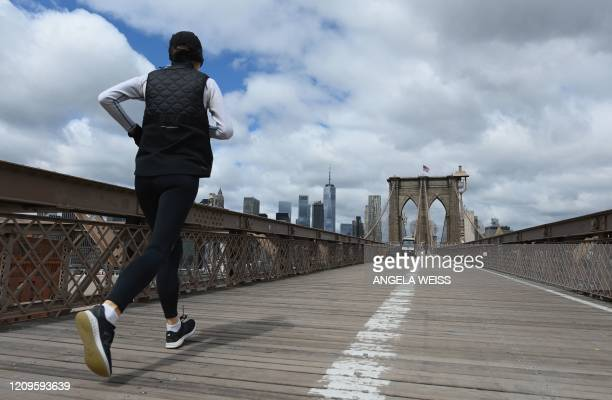 Woman jogs over the nearly empty Brooklyn Bridge on April 10, 2020 in New York City. - Hundreds of millions of people around the world will spend the...