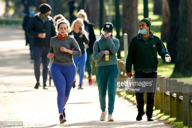 A woman jogs past a couple walking at Princes Park on July 25 2020 in Melbourne Australia Victoria reported seven COVID19 deaths on July 24 the...