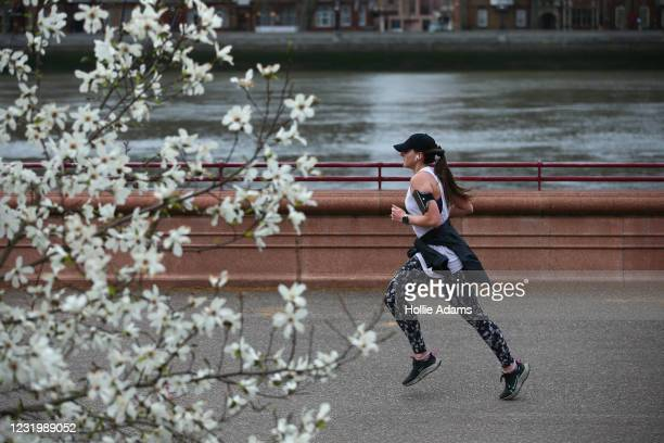 Woman jogs past a flowering tree in Battersea Park on March 28, 2021 in London, England. Starting tomorrow, England will ease its rules on...