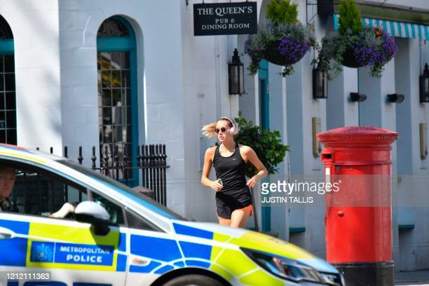 A woman jogs past a police car near Primrose Hill in London on May 7 2020 as life continues in Britain under a nationwise lockdown to slow the spread...