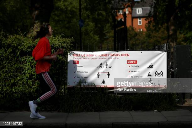 A woman jogs past a sign asking the public to keep the park open at London Fields on May 07 2020 in London England The UK is continuing with...