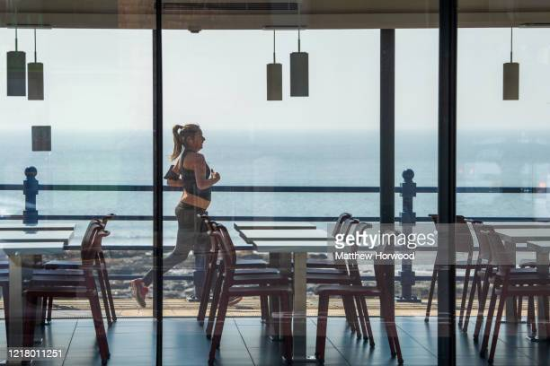 A woman jogs past an empty cafe on the seafront on April 10 2020 in Porthcawl United Kingdom Police have stepped up patrols to prevent people from...