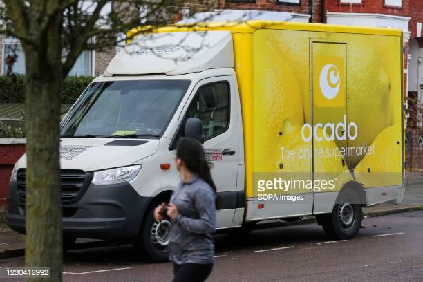Woman jogs past an Ocado delivery van in London.