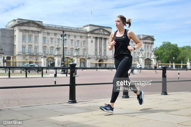 Woman jogs past Buckingham Palace in central London on May 26 as lockdown measures are eased during the novel coronavirus COVID-19 pandemic.