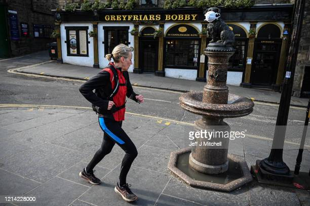 A woman jogs past Greyfriars Bobby statue which has a mask placed over its face on March 23 2020 in Edinburgh Scotland Coronavirus has spread to at...