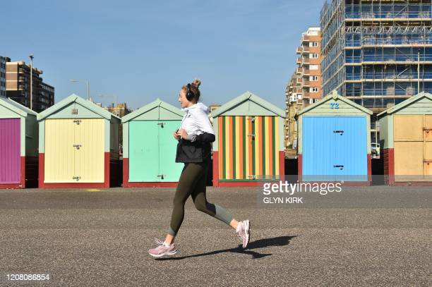 A woman jogs past painted sheds on the seafront in Brighton southern England on March 24 2020 after Britain ordered a lockdown to slow the spread of...