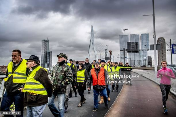A woman jogs past protestors wearing yellow vests demonstrating on the Erasmusbrug in Rotterdam The Netherlands on December 8 2018 The socalled...