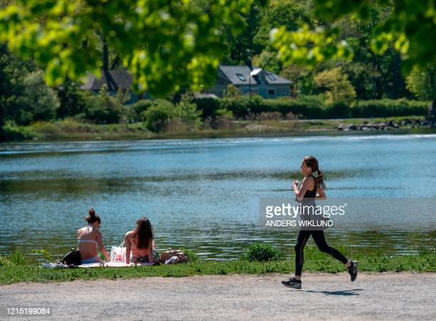 Woman jogs past sunbathers next to a canal at Djurgarden in Stockholm, on May 26 as temperatures reached 20 degrees Celsius. / Sweden OUT