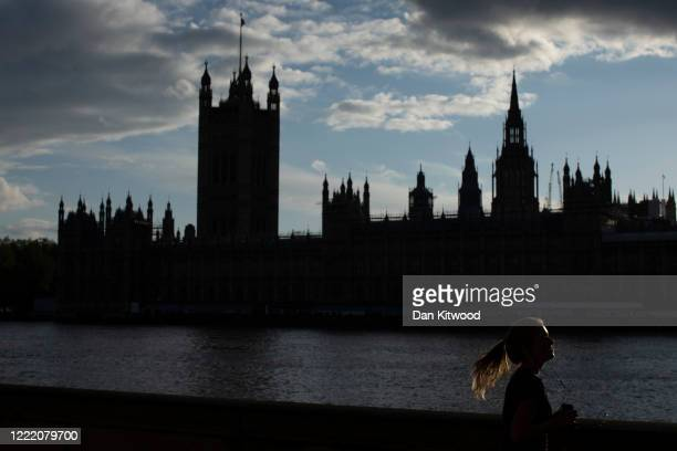 A woman jogs past the Houses of Parliament on April 30 2020 in London England British Prime Minister Boris Johnson who returned to Downing Street...
