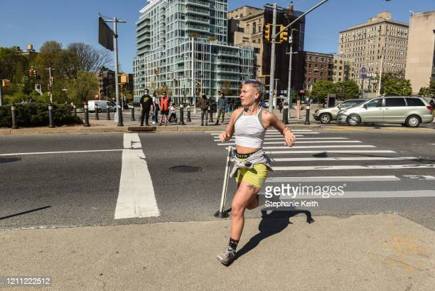 Woman jogs towards Prospect Park on April 28, 2020 in the Brooklyn borough in New York City. New York City Parks Department has kept the parks open,...