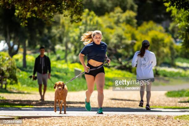 Woman jogs with her dog along the Hermosa Valley Greenbelt, in Hermosa Beach, CA, March 26 even after Gov. Gavin Newsom declared his policy of safer...
