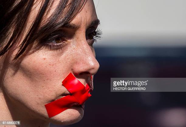 A woman joins hundreds wearing black shirts and bearing red tape on their mouths during the third annual edition of the Walk for Freedom against...