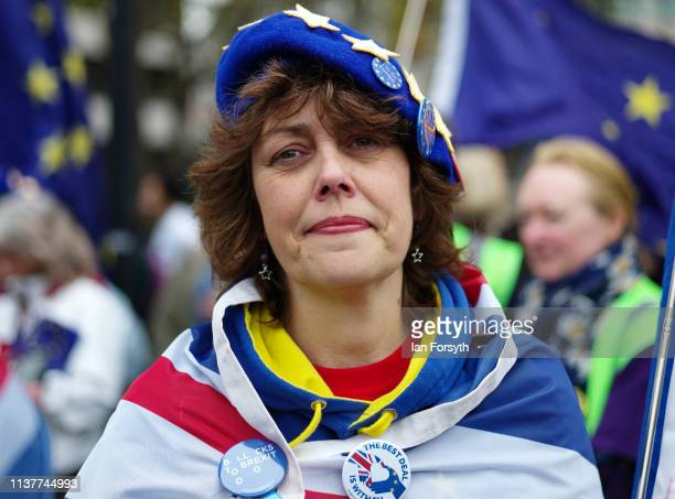 A woman joins thousands of demonstrators as they prepare to take to the streets of London during the People's Vote March on March 23 2019 in London...
