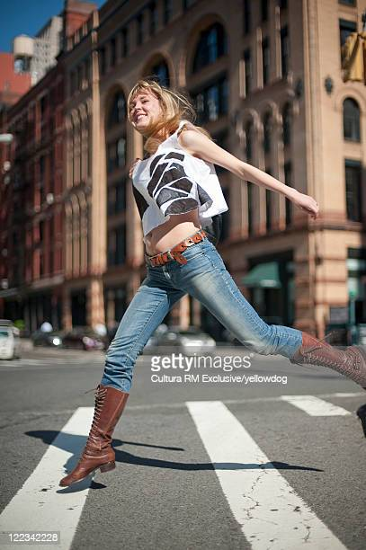 Woman joyfully crossing city street