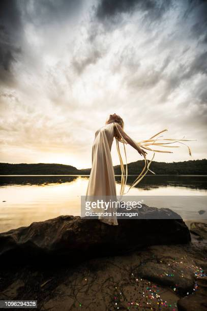 a woman joyfully laughs up at the sky by a lake - mystic goddess stock photos and pictures