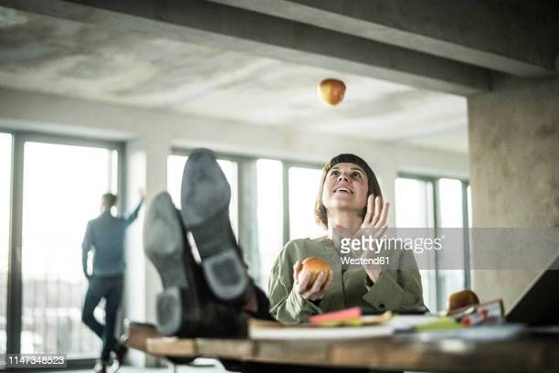 woman juggling apples in the office, sitting with feet on desk - unabhängigkeit stock-fotos und bilder