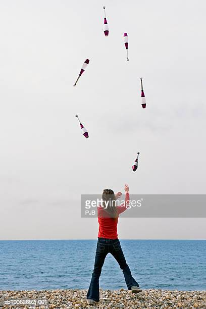 Woman juggling on beach, rear view