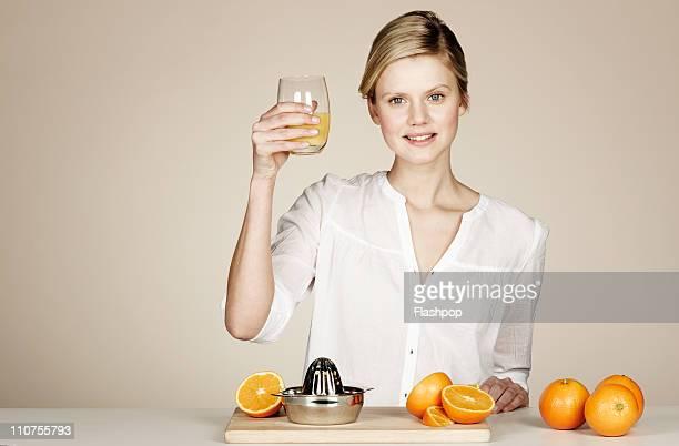 Woman juicing fresh oranges